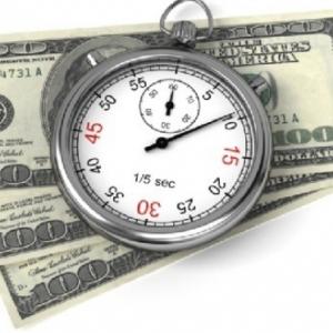 Часы на фоне денег как символ экспресс кредита
