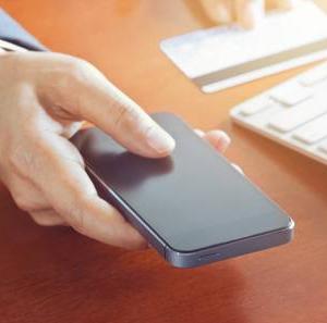 Мужчина заполняет заявку на займ через телефон